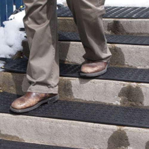 Person walking on stair case covered with HOT-flake heated mats
